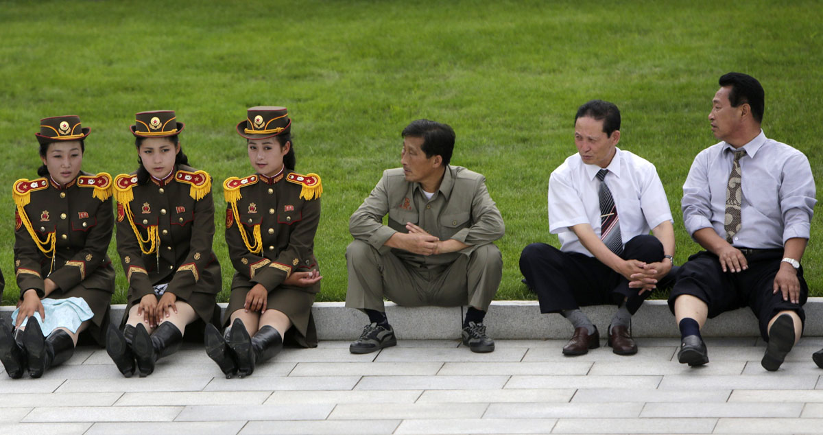 North Korean men look at members of a military band in Pyongyang