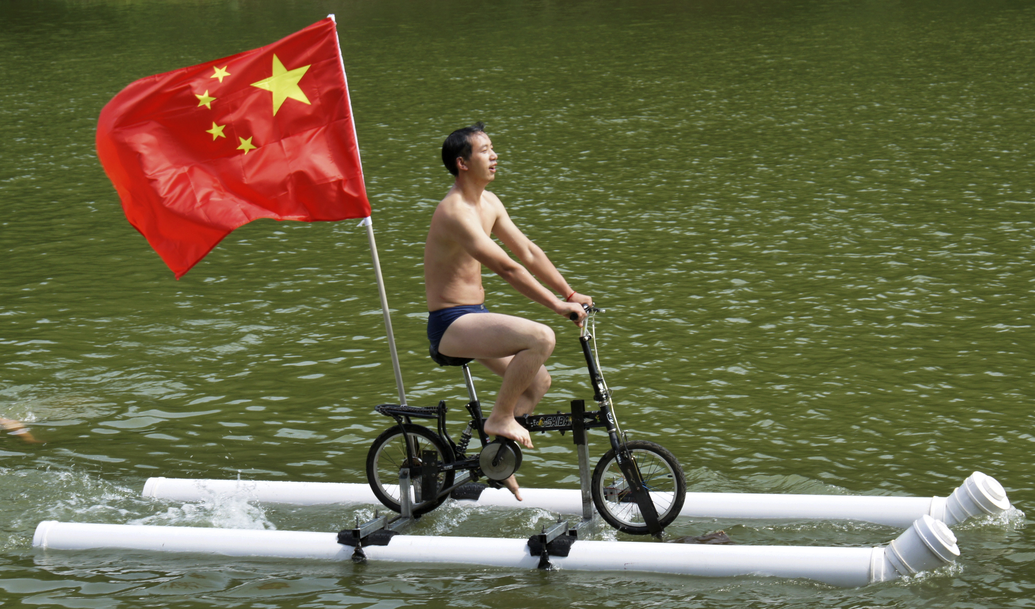 A Chinese flag is seen as Liu Wanyong performs on his invention, an improvised bicycle which is held afloat by plastic tubes, in Zhenning